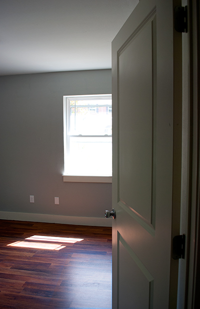 Entrance to a grey toned empty bedroom.